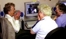 Três senhoras interagindo com um PC