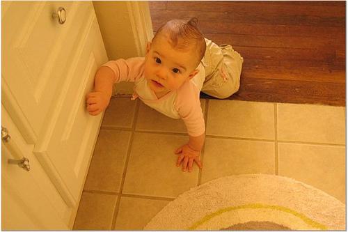 Um bebê tenta abrir uma gaveta