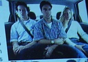 Tres passageiros sentados no banco de tras de forma desconfortavel