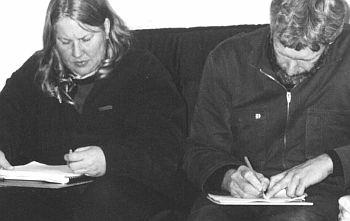 Pessoas preenchendo formulários em papel com visível desconforto.